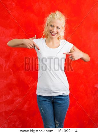 Woman in white round neck T-shirt on red background pointing at it with both hands