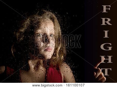 fright written on virtual screen. hand of frightened young girl melancholy and sad at the window in the rain