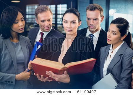 Lawyer reading law book and interacting with business people in office