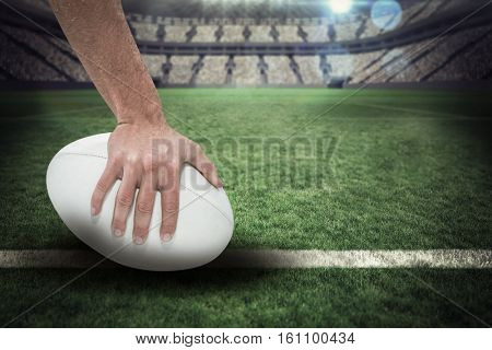 Close-up of sports player holding ball against rugby pitch 3D