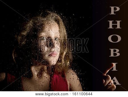 phobia written on virtual screen. hand of frightened young girl melancholy and sad at the window in the rain