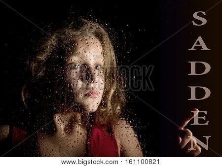 sadden written on virtual screen. hand of frightened young girl melancholy and sad at the window in the rain