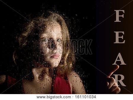 fear written on virtual screen. hand of frightened young girl melancholy and sad at the window in the rain