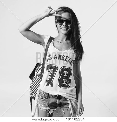 Young woman in sunglasses saluting showing v sign looking at camera. Portrait of trendy girl having fun style casual concept lifestyle urban fashion