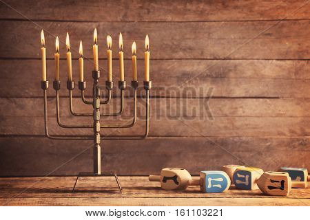 Menorah with candles for Hanukkah on table against wooden background