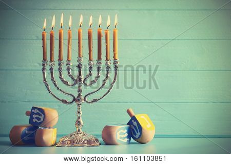 Menorah with dreidels for Hanukkah on table against wooden background