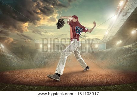 Baseball playerin red in action on the stadium under sky with clouds.