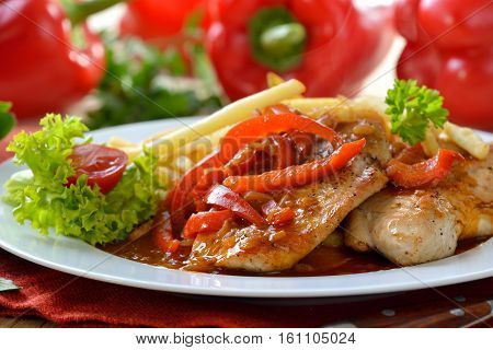 Hot escalope of turkey with red pepper sauce (so-called 'Zigeunerschnitzel) and French fries
