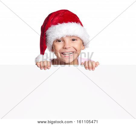 Smiling little boy wearing Santa Claus hat, holding white board - happy child peeking over edge of blank empty paper with copy space.