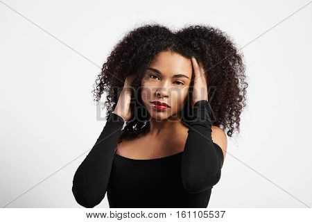 Black Woman With Ideal Skin Touching Her Black Curly Hair