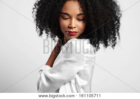 Young Black Woman With Curly Hair Watching Down