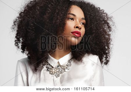 Black Woman Watching Aside With Ideal Skin And Curly Hair