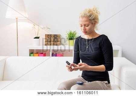 Woman sitting on couch and using diabetes needle