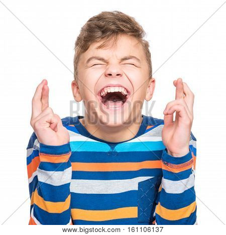 Close-up portrait of handsome hopeful teen boy crossing his fingers. Beautiful human face expression and emotions. Funny caucasian child making luck gesture with eyes closed, isolated on white background.