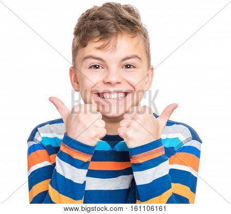 Close up emotional portrait of caucasian smiling teen boy making thumbs up gesture. Head shot of handsome funny teenager, isolated on white background. Happy child looking at camera.