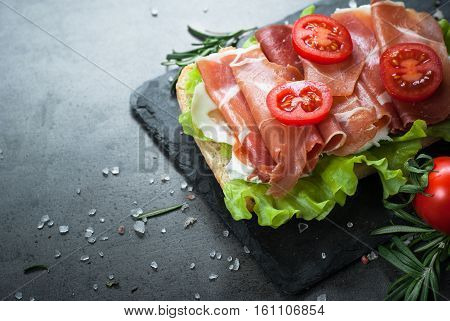 Ciabatta sandwich with  salad leaves jamon serrano and mozzarella cheese over stone background. Mediterranean Food background.