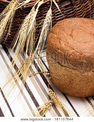 Round loaf of bread with wheat ears near the wicker basket