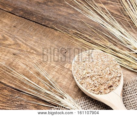 Wooden spoon with wheat bran and wheat ears. Dietary supplement to improve digestion. Copy space