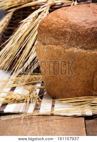 Round loaf of freshly baked bread with wheat ears on striped cloth napkin and wooden planks near the wicker basket. Close-up, shallow depth of field