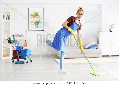 Funny adult woman moping floor in living room