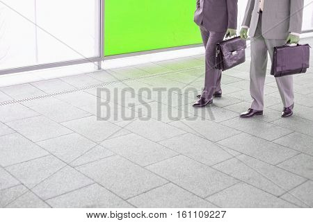 Low section of businessmen communicating while walking in railroad station