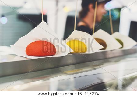 Fresh colored burger buns with wooden sticks. Colorful bread for hamburgers row on counter. Vendor street fast food.
