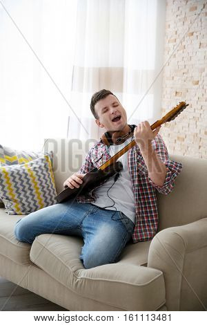 Young man in headphone enthusiastically playing the electric guitar in a light room