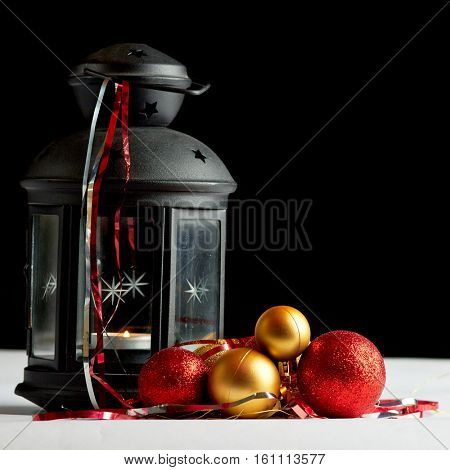 Christmas still life with balls and candlelight lamp