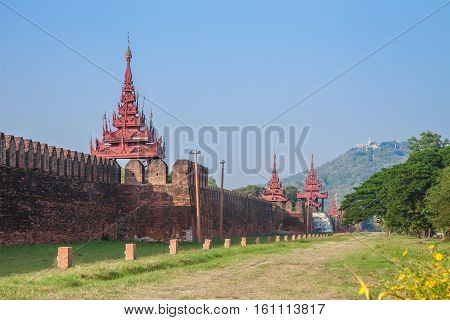 Wall of Mandalay Royal Palace and Mandalay Hill in background in Myanmar.