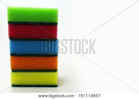 Multicolored sponges for washing dishes on a white background