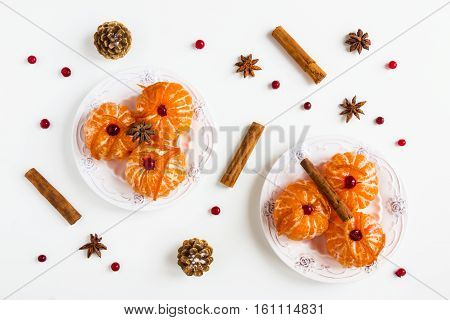 Christmas background peeled whole tangerine in caramel citron cinnamon sticks anise stars on white top view flat lay.