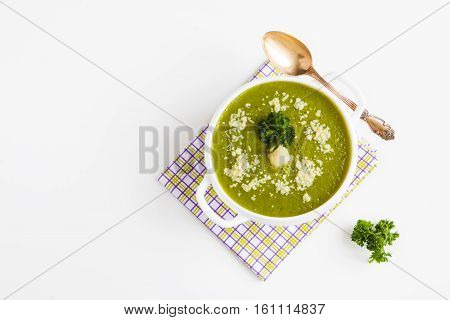 Portion of homemade diet cream soup of cauliflower and green beans in a bowl with grated Parmesan cheese and fresh parsley. Vintage spoon white table top view.