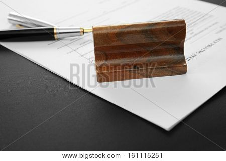Stamp, document and pen on notary public table