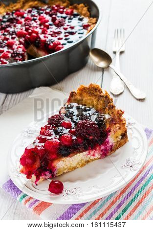 Open round cake with berries raspberries blackberries red and black currant jelly. Shortbread dough a layer of cheese. White wooden table.