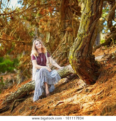Beautiful Young Romantic Girl Sitting On The Tree Trunk