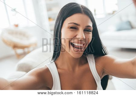 Having fun at home. Self portrait of young beautiful woman looking at camera and smiling while sitting on the couch at home