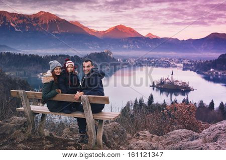 Family travel Slovenia Europe. Bled Lake one of most amazing tourist attractions. Winter landscape. Top view on Island with Catholic Church in Bled Lake with Castle and Alps Mountains in Background.