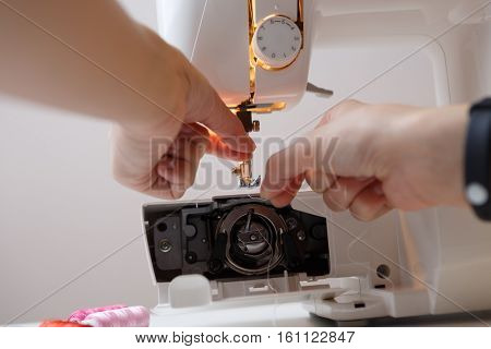 Woman prepares sewing-machine to work