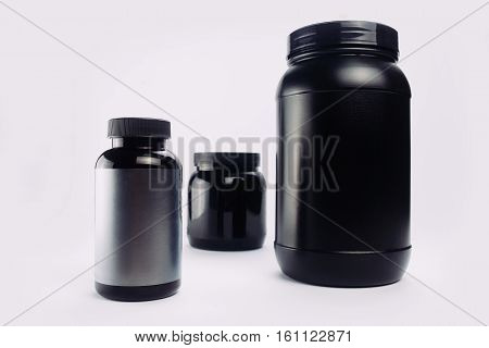 Sport Nutrition Whey Protein and Gainer. Black Plastic Jars isolated on white background