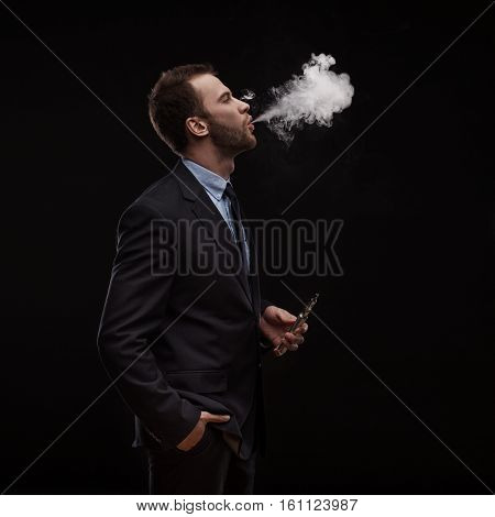 young businessman blowing smoke of electronic cigarette on dark background