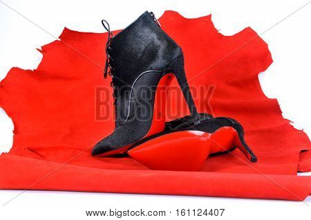 Ukraine Kiev - August 25 2016: Women's boots handmade on a piece of material from the red skin. Imitation brand shoes Christian Louboutin showing red soles - illustrative editorial