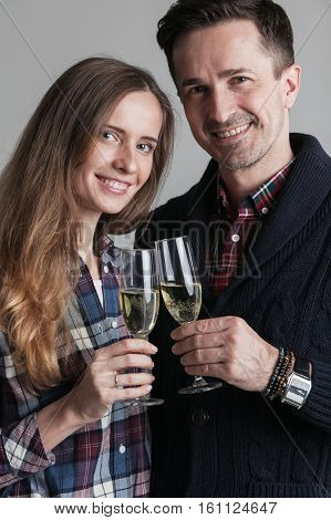 Happy couple in casual clothes clinking champagne celebrating new year
