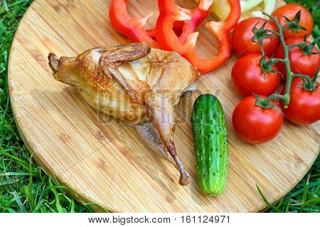 Delicious fried quail with fresh juicy vegetables on the wooden round board on green grass. Prepared tomato, cucumber, sweet pepper, partridge, quail. Roasted Partridge, quail grilling on sunny day. Culinary concept with delicious food.