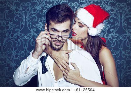 Sexy santa woman seduce young man in tux at Christmas