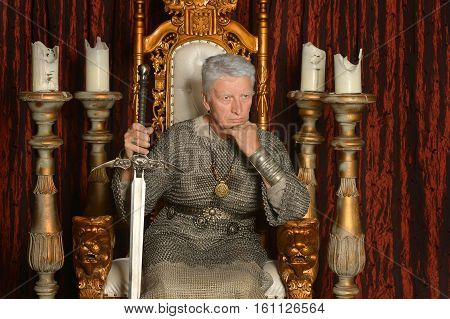 Mature pensive medieval knight on the throne