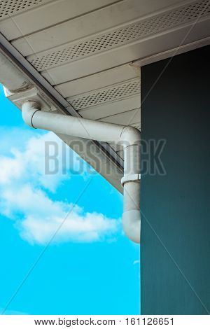 White rain gutter. Drainage System with Plastic Siding Soffits and Eaves against blue sky.