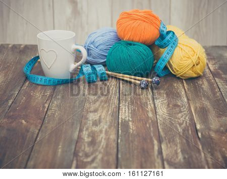 Yarn with wooden knitting needles for knitting on wooden background