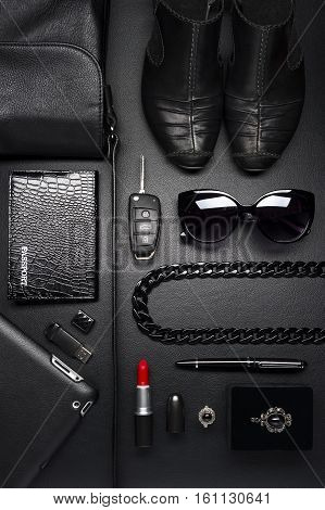 Woman accessories in business style, red lipstick, gadgets, shoes, jewelry, car key, bag, eyewear and other luxury businesswooman attributes on leather black background, fashion industry, top view