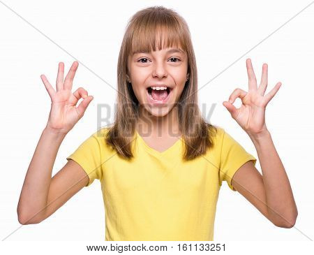 Close-up emotional portrait of attractive caucasian girl. Beautiful happy schoolgirl making ok gesture and looking at camera. Funny cute smiling child, isolated on white background.