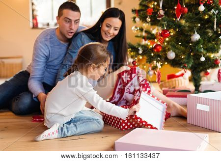 Beautiful young family with little daughter at Christmas tree at home unpacking presents.